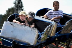 Conner Rothrock, 6, left, Jessica Brandenburg, 12, and Alex Brackens, 9, ride the children's roller coaster May 19 during Armed Forces Day on JBLM.