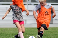 Soccer camp participant Sarah Mitchell, 7, chooses to wear an orange pinney over her head during a youth soccer camp scrimmage with teammate Drew Carlson, 6.