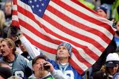 "Martin McDonough, of Port Orchard, waves the flag to honor service members during the Seahawks-Jets game Sunday at CenturyLink Field in Seattle. It was the NFL's annual ""Salute to Service"" day."