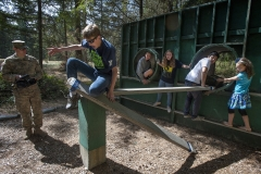 "Peter Vosselmann, 14, middle, looses his grip while attempting to position a wood plank for his teammates to cross to complete the ""Rat Hole"" obstacle Aug. 24 during an 84th CAB Community Connector event at the JBLM Field Reaction Leader Course on Lewis Main."