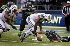 Seahawks quarterback Russell Wilson (3) scrambles to recover his own fumble before Jets linebacker Ricky Sapp (55) can fall on it.
