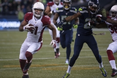 Cardinals receiver Larry Fitzgerald, left, races past Seahawks defender Richard Sherman, right, after making a first-half reception Nov. 15 during Arizona's 39-32 win at CenturyLink Field in Seattle.