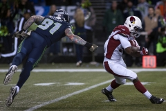 Cardinals running back Andre Ellington, right, slips past Seahawks defensive end Cassius Marsh (91) Nov. 15 during the Seattle's 39-32 loss to the Arizona Cardinals at CenturyLink Field in Seattle.