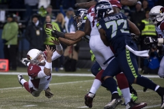 Seahawks linebacker K.J. Wright, middle, snags a bouncing ball away from Cardinals quarterback Carson Palmer, left, after a strip sack fumble Nov. 15 during Arizona's 39-32 win at CenturyLink Field in Seattle.