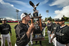 Army's Corey Nottingham, middle, kisses the championship trophy after winning the annual Salute to Armed Forces Softball Classic at Cheney Stadium in Tacoma. Army defeated Navy 20-6.
